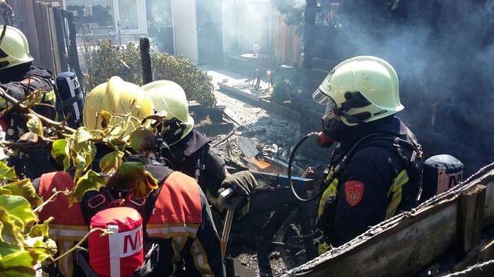 De brandweer blust de brand. Van het schuurtje is helaas weinig meer over.
