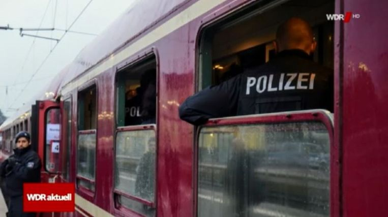 De politie ondervraagt passagiers over de flessenwerper.