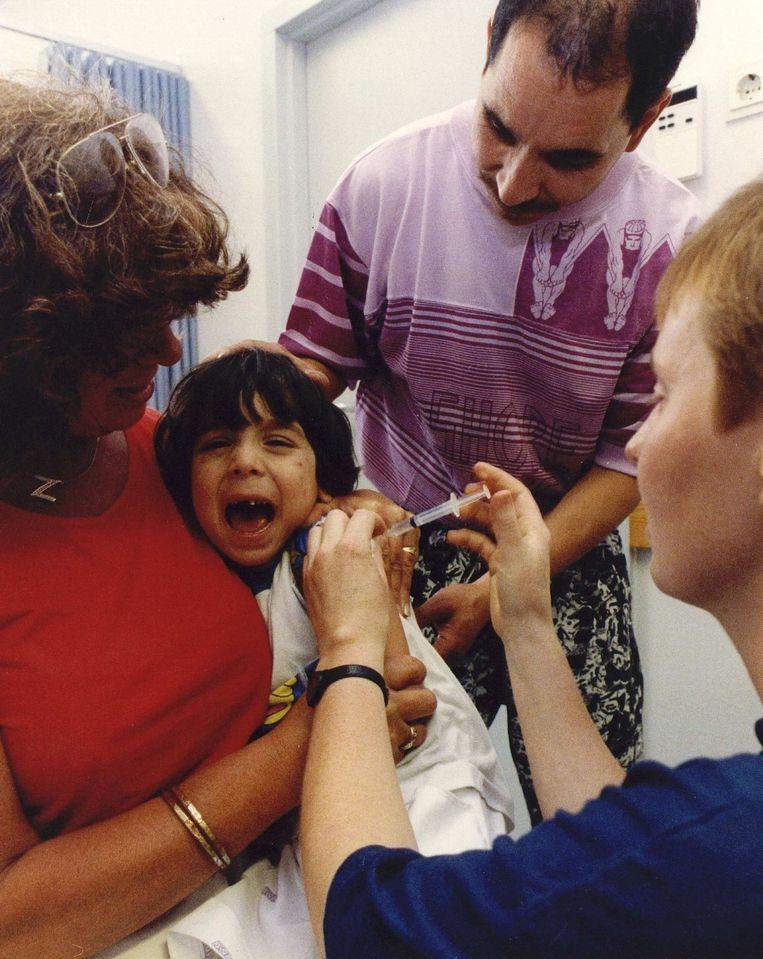 Een meisje wordt in het bijzijn van haar ouders ingeënt tegen Hepatitus A en tyfus. Beeld anp