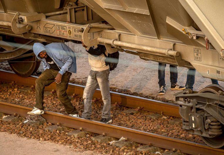 Migranten verbergen zich onder een goederentrein die via de Eurotunnel naar Engeland gaat.