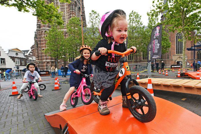 OOSTERHOUT - De tweejarige Yara heeft plezier voor twee als ze voorop gaat op de pop-up crossbaan op de Markt in Oosterhout.