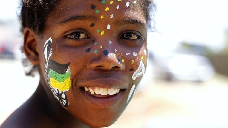 Een vrouw heeft haar gezicht beschilderd in de kleuren van het ANC. Beeld reuters