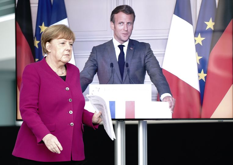 Bondskanselier Angela Merkel arriveert op een persconferentie waarbij de Franse president Emmanuel Macron via videoverbinding aanwezig is.   Beeld DPA
