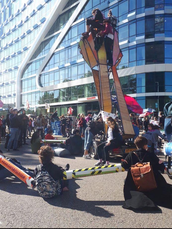 Demonstranten zitten op de weg en aan elkaar vastgeketend met extra lange lockons om 1,5 meter afstand te houden.
