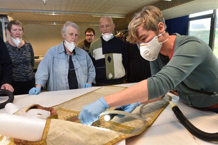 Met een speciale museumstofzuiger maakt Leen Lombaert, depotconsulent bij de provincie Oost-Vlaanderen de gewaden proper.