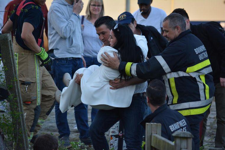 De brandweer moest de reizigers, waaronder deze vrouw, over een smal paadje aan de achterzijde van een winkel helpen.