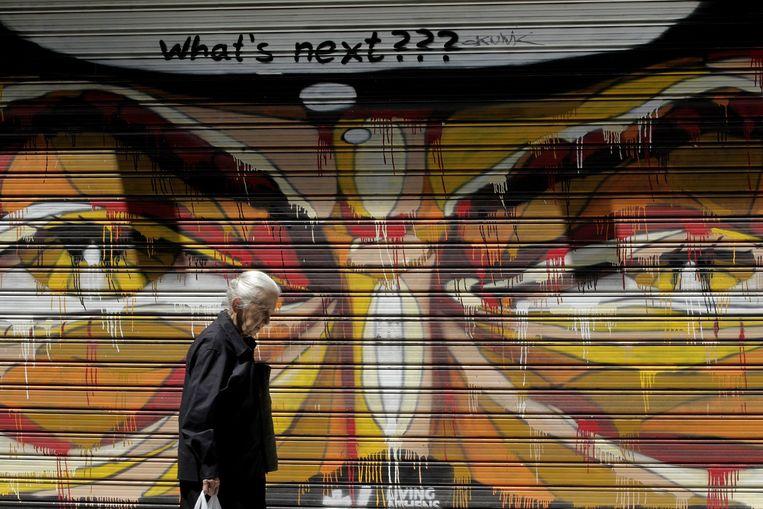 Een oudere vrouw wandelt over straat in Athene. Beeld epa