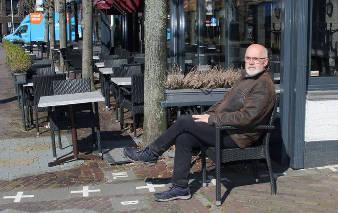 Burgemeester Frans De Bont op een stoeltje pal op de grens.