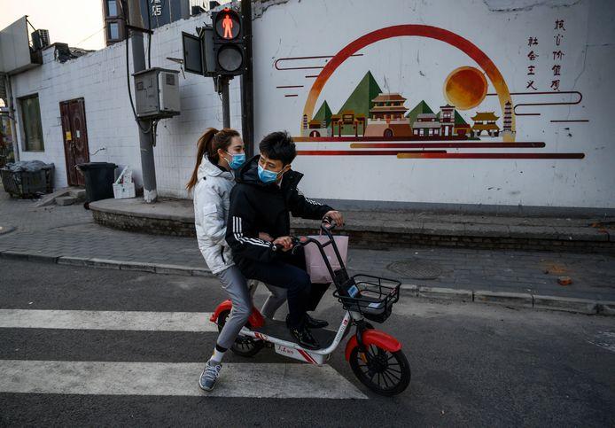 Een stel op de scooter in Peking gisteren.