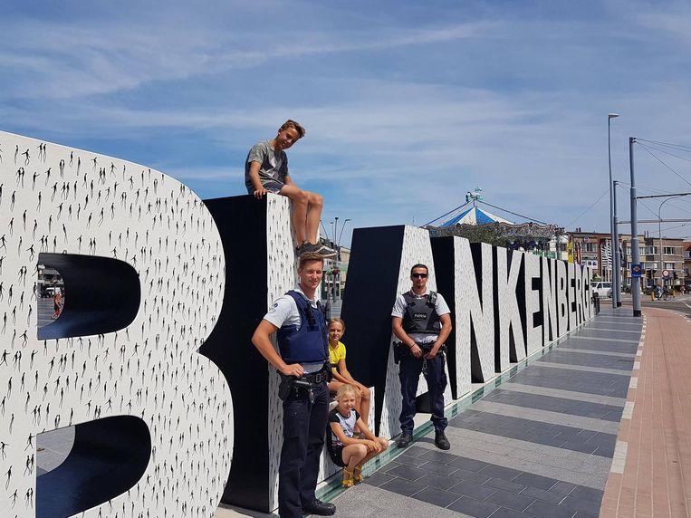 Enkele kinderen zitten op de letters onder het toezicht van de politie.