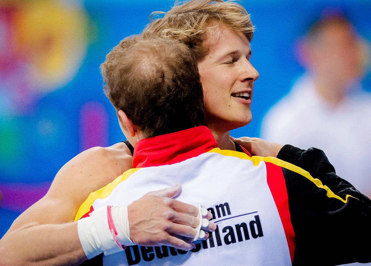Epke Zonderland krijgt felicitaties van zijn voornaamste concurrent Fabian Hambüchen op het EK turnen in Sofia.