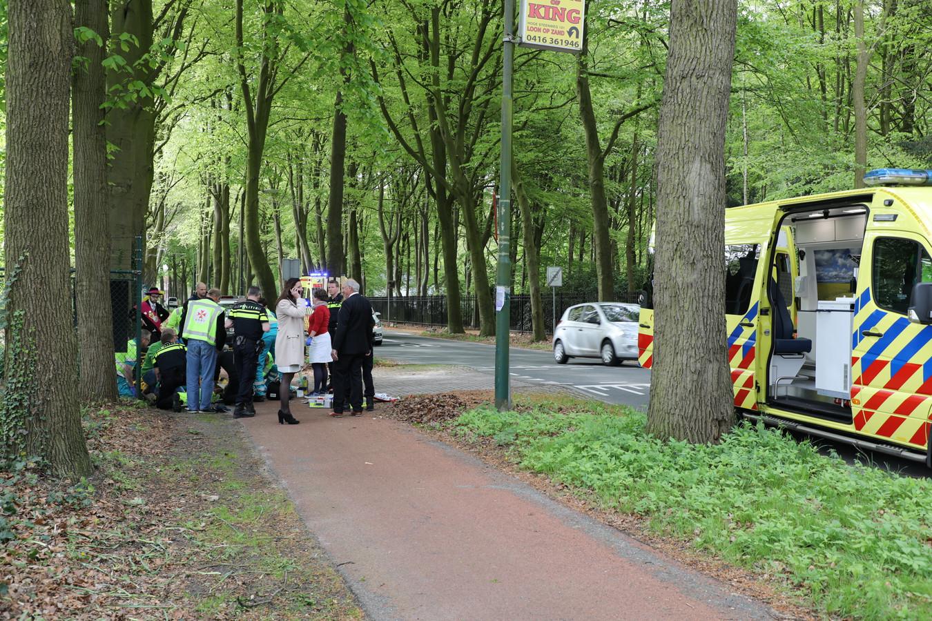 Burgemeester Hanne van Aart (in witte jas) belt terwijl ambulancemedewerkers zich over het slachtoffer ontfermen.