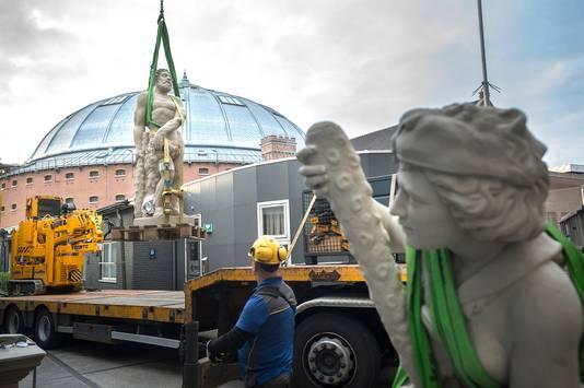 De gerestaureerde Hercules wordt onder toeziend oog van Omphale op een vrachtwagen getakeld op weg naar het Emile van Loonpark in Roosendaal. Raymund Bervoets restaureerde de beelden nadat ze door vandalen zwaar waren beschadigd. Foto Pix4Profs-Ron Magielse