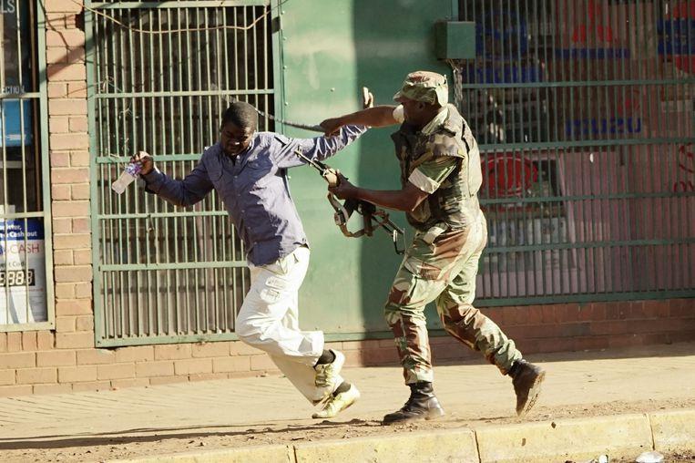 Een militair slaat een demonstrant in Harare. Beeld AFP