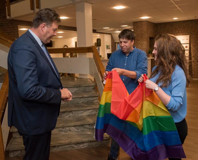 De Regenboogvlag werd maandagavond overhandigd aan burgemeester Breunis van de Weerd (l.).