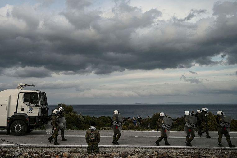 De Griekse oproerpolitie trekt zich terug na botsingen met demonstranten tijdens protesten tegen de bouw van een nieuw controversieel migrantenkamp in de buurt van de stad Mantamados op Lesbos. Beeld Aris Messinis, AFP