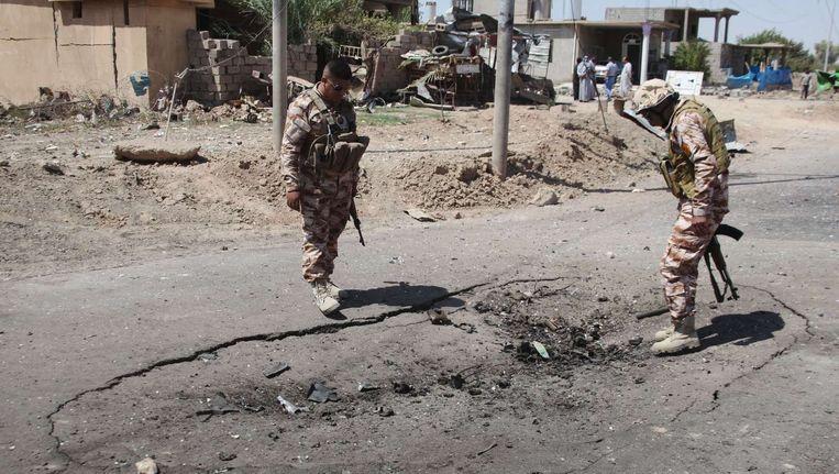 Iraakse Peshmerga-strijders inspecteren de plaats waar een bomauto ontplofte in Kirkuk, gisteren.
