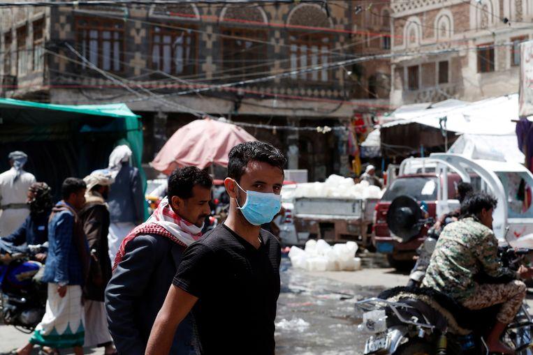 Jemenieten lopen op een markt in Sanaa waar nu al vijf jaar oorlog woedt.   Beeld EPA