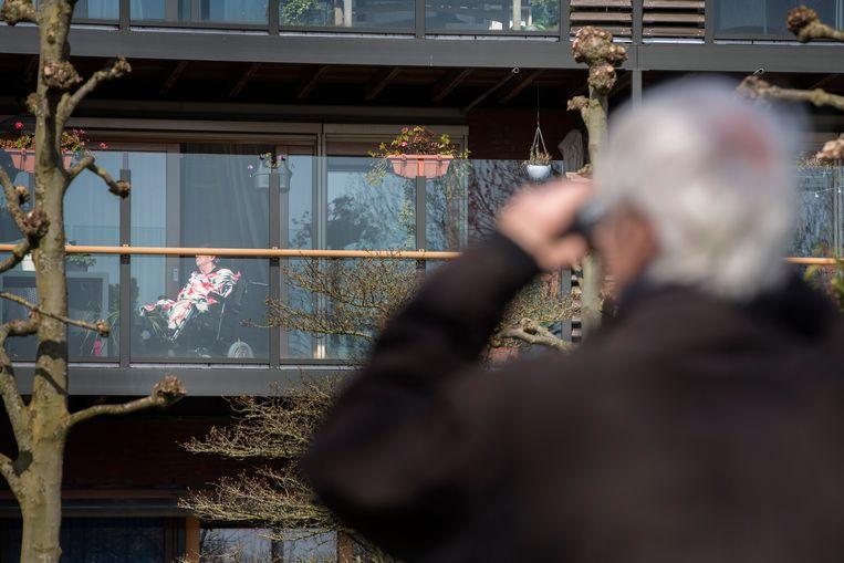 Oud-huisarts Charles Koning (83) keek twee weken naar zijn demente vrouw Adriana door de verrekijker, omdat hij niet in het verpleeghuis in Hendrik-Ido-Ambacht op bezoek mocht. Ze kennen elkaar sinds 1956 en zijn bijna 58 jaar getrouwd - ze zijn nooit eerder van elkaar gescheiden geweest. Beeld Werry Crone / Hollandse Hoogte.