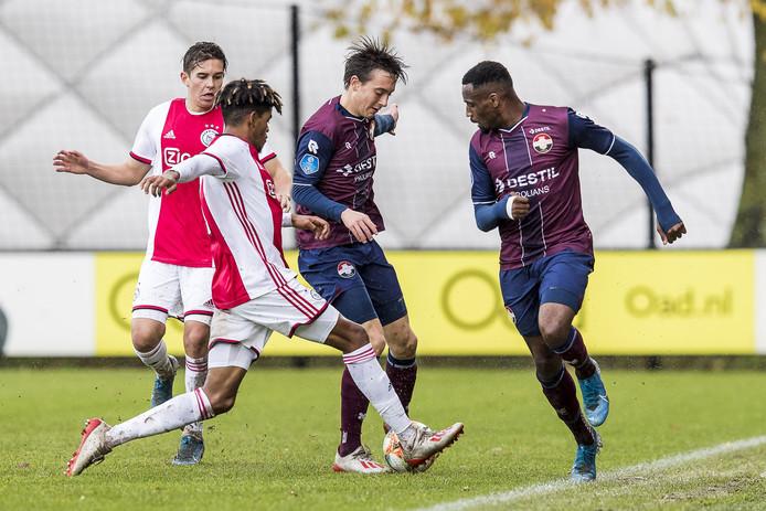 Ajacied Dean Solomons in duel met Willem II'er Rick Zuijderwijk. Rechts Elton Kabangu.