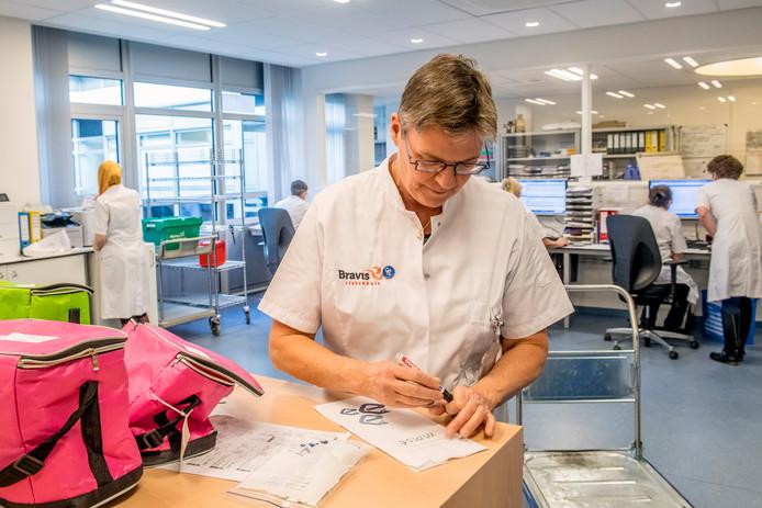 Apothekers-assistent Gera Kersjes  van de Bravis ziekenhuisapotheek druk in de weer met het gereedmaken, verzamelen en controleren van medicatie voor cliënten van zorginstellingen in de regio.
