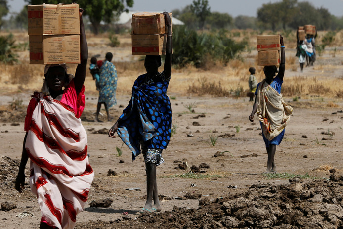 Vrouwen dragen dozen met voedsel in Zuid-Soedan.