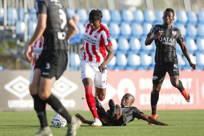 Noni Madueke (PSV, midden) in duel met spelers van KAS Eupen.