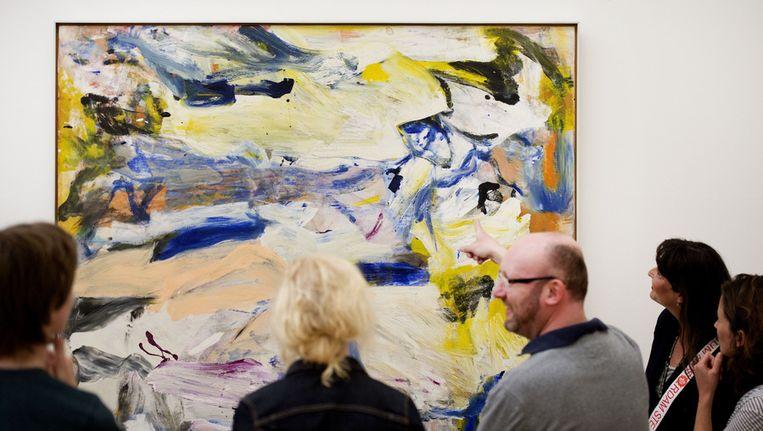Bezoekers van het Stedelijk Museum kijken naar werk van Willem de Kooning. Beeld anp