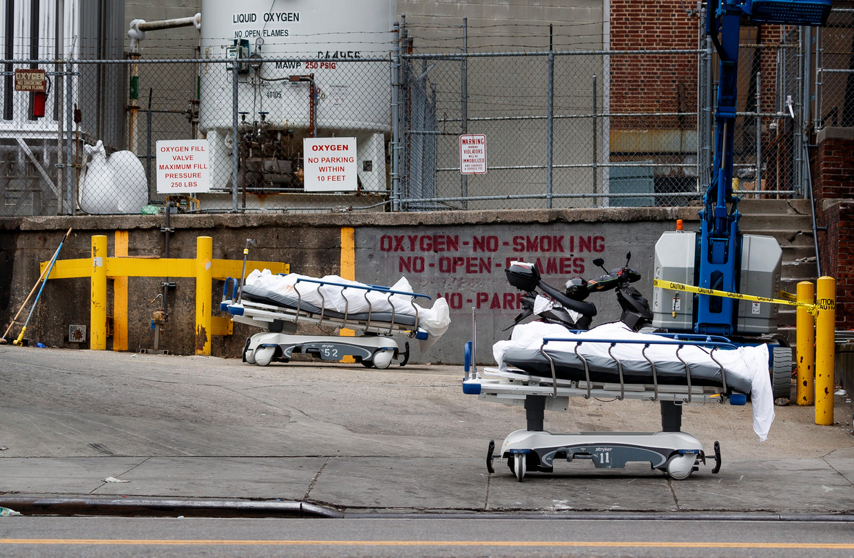 Twee overleden patiënten staan geparkeerd achter een ziekenhuis in Brooklyn. Beeld EPA