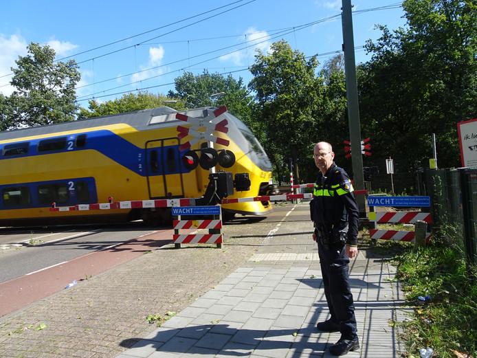 Wijkagent Marcel de Rouw bij spoorwegovergang Wolfskamerweg.