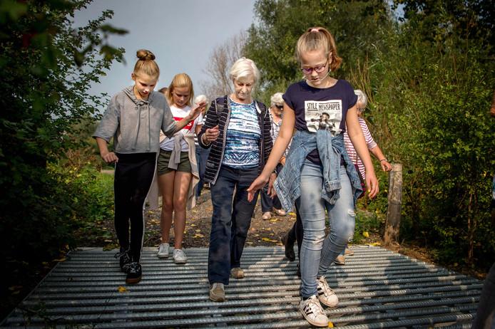 Jongeren van groep 8 gaan wandelen met de ouderen uit het dorp. Riet Hendriks (3e van links) en Imme Teppenbroek (geheel links) leren elkaar kennen.