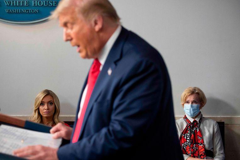 Topadviseur Deborah Birx (rechts, met mondkapje) en Trumps woordvoerder (links) bij een persconferentie van de Amerikaanse president afgelopen maand.  Beeld AFP