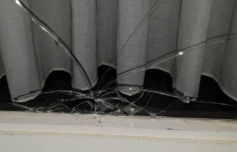 Het beschadigde raam nadat er een fiets tegen werd gegooid.