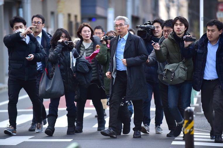 Advocaat Junichiro Hironaka omgeven door pers. Beeld AFP