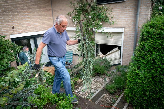 Cor Smit en Ted Rijsemus uit Huissen helpen een alleenstaande buurvrouw met het opruimen van haar tuin. Een ruit is gesneuveld.
