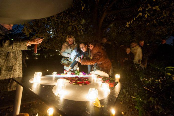 Bezoekers van een vorige editie aan Verbonden in Licht steken bloemen in het hart bij het monumentje voor het ongedoopte kind.