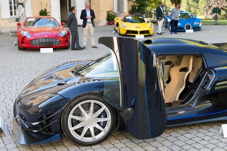 Obiangs Koenigsegg One 1 werd ook geveild. Achterin van links naar rechts: eenAston Martin One 77, een Ferrari F150 en een Bugatti Veyron EB. Beeld Laurent Gillieron/AP