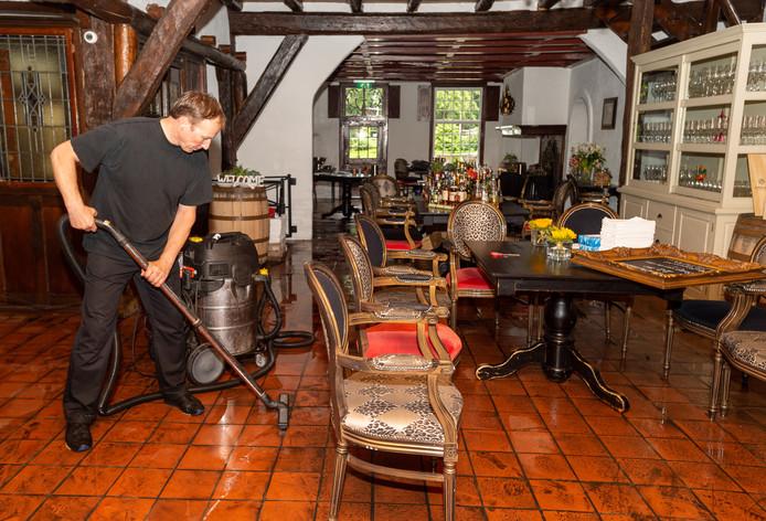 Met de waterstofzuiger zuigt André Licht het water zo goed mogelijk weg uit zijn restaurant.