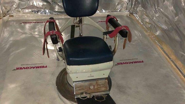 Tandartsstoel in de martelkamer die werd ontdekt bij een inval in een loods in het Brabantse Wouwse Plantage. Omliggende zeecontainers waren als cel ingericht. Beeld ANP Handouts
