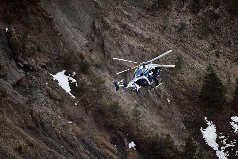 Een helikopter zoekt naar wrakstukken in de Alpen. Beeld afp