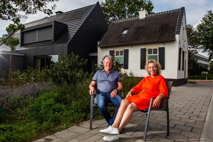 Frank en Marieke Elders met op de achtergrond het oudste tolhuisje van Raalte, waar ze hun nieuwbouwwoning aan hebben gebouwd.