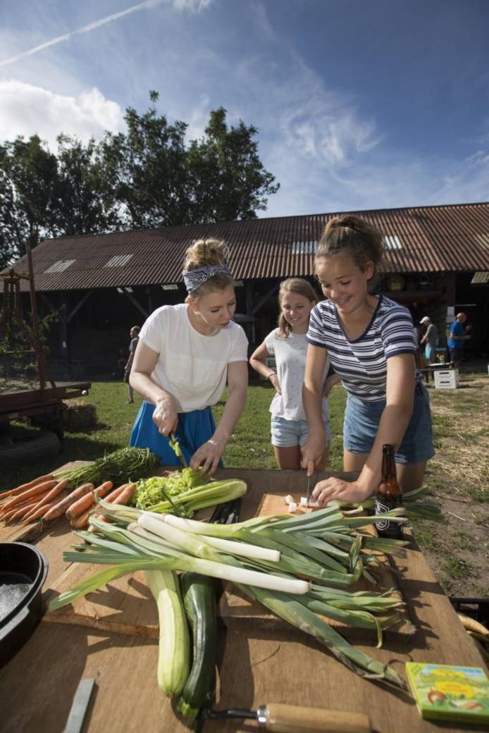 Estée Strooker (links) laat bezoekers zien hoe je het best groente kunt snijden.