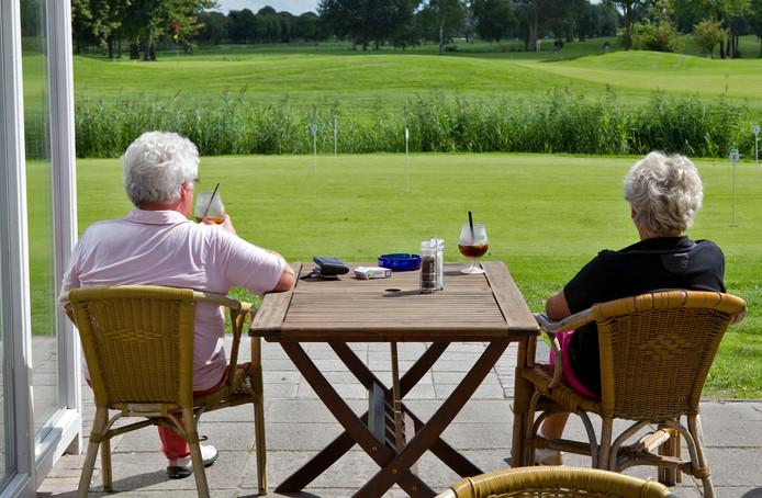 Ouderen genieten van een drankje op een terras bij de golfbaan in Amsterdam. Pensioenfondsen waarschuwen dat miljoenen gepensioneerden gekort zullen worden.