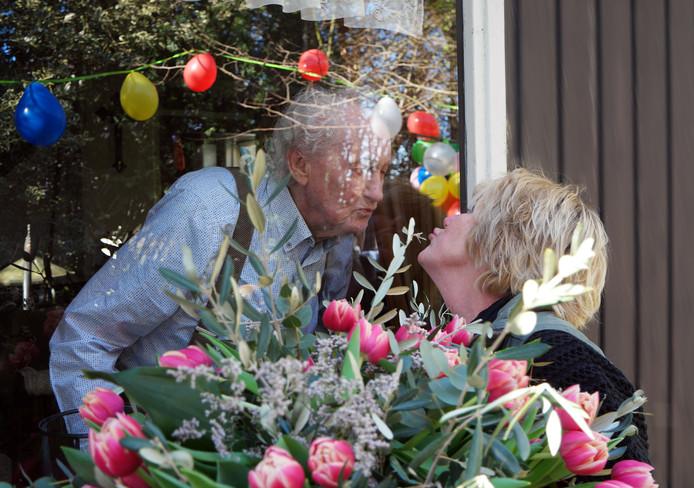 Nicky Markslag feliciteert haar vader Gerrit Markslag met zijn verjaardag. Vanachter het raam, vanwege het coronavirus