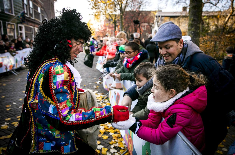Een roetveegpiet deelt pepernoten uit tijdens de landelijke intocht van Sinterklaas op de Zaanse Schans.