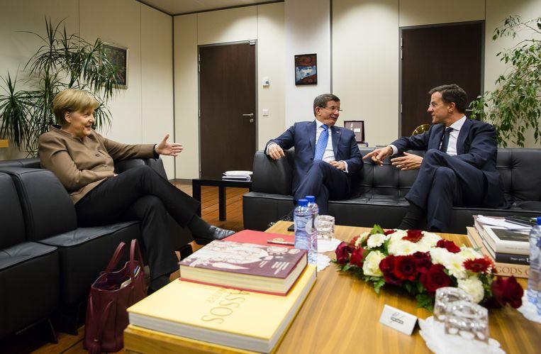 Mark Rutte en Angela Merkel onderhandelden in maart 2016 namens de EU met de Turkse minister Ahmed Davutoglu over een migratiedeal. Beeld Anp