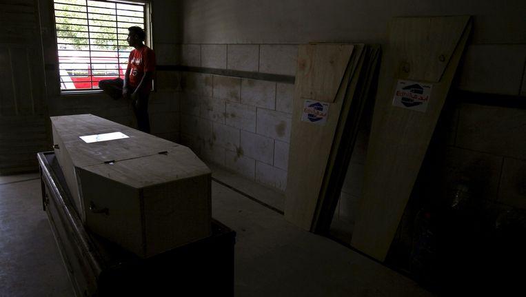 Een vrijwilliger wacht bij de kist van een van de 120 dodelijke slachtoffers van de extreme hitte in Karachi. Beeld reuters