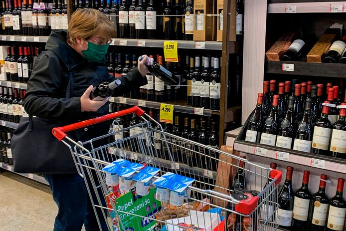 A woman buys wine at a supermarket in Santiago, on June 17,2020. - After a difficult and unforgettable harvest due to mobility restrictions and the decision to speed up the harvest with winemakers armed with masks and alcohol gel on hand, Chilean winemakers hope to produce better quality wines during the COVID-19 pandemic. (Photo by MARTIN BERNETTI / AFP)