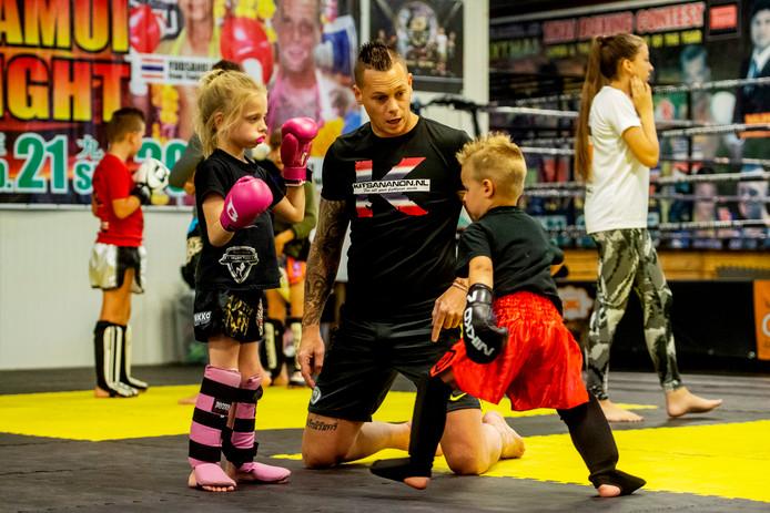Sportschooleigenaar Joey Smits geeft in de training uitleg aan de kleinste sporters van de sportschool.