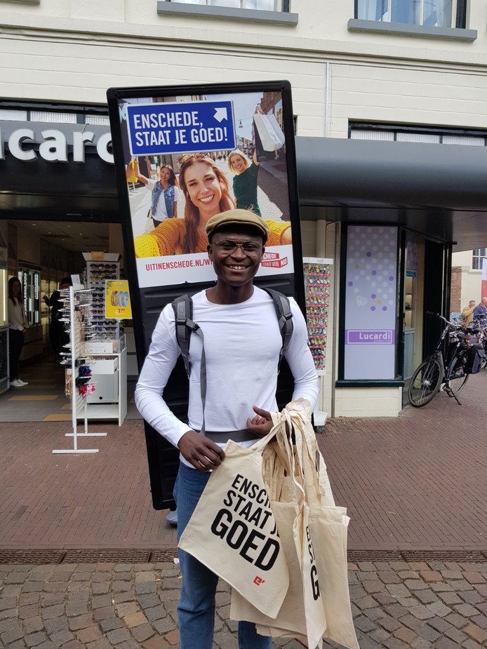 Met een groot reclamebord op de rug, probeert deze jongeman het winkelend publiek in Winterswijk voor Enschede te interesseren.